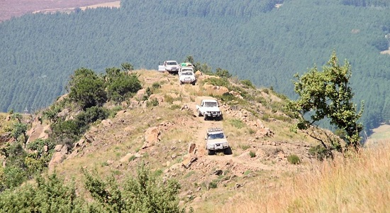 A group of Toyota Land Cruisers ascending the pass