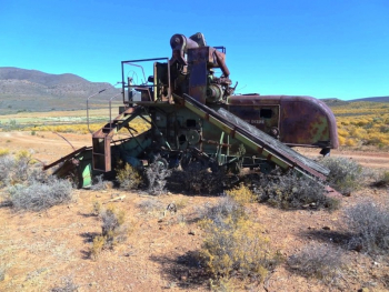 An abandoned John Deere thresher near the roadside